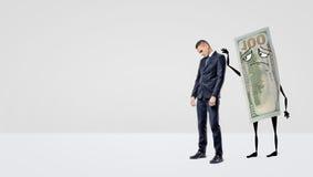 Un hombre de negocios triste que es asegurado por un billete de dólar grande con los brazos y las piernas que acaricia a la parte Fotografía de archivo libre de regalías