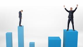 Un hombre de negocios triste se prepara para reducir en una columna baja y un ganador al lado de él que acaba de intensificar en  Imagen de archivo