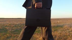 Un hombre de negocios va a trabajar por la ma?ana con una cartera a trav?s del parque hombre en traje de negocios con la cartera  almacen de metraje de vídeo