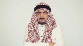 Un hombre de Oriente Medio con una barba mira cuidadosamente y sacude su cabeza de lado a lado manos dobladas en su pecho almacen de video