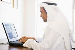 Un hombre de Oriente Medio delante de un ordenador Imagen de archivo libre de regalías