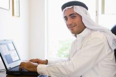 Un hombre de Oriente Medio delante de un ordenador Foto de archivo libre de regalías