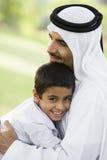 Un hombre de Oriente Medio y su hijo que se sientan en un parque fotografía de archivo libre de regalías