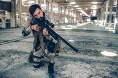 Un hombre de pelo oscuro se está colocando en hangar largo solo Él ha puesto una rodilla abajo en la tierra y el sostenerse rifle Fotos de archivo