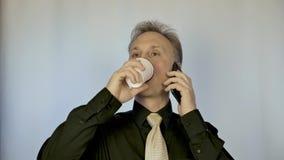 Un hombre de tamaño mediano bebe el café y negociaciones sobre el teléfono Él lleva negociaciones del negocio almacen de video