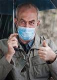 Un hombre debajo de un paraguas en la lluvia, en la máscara médica de la cara Imagen de archivo