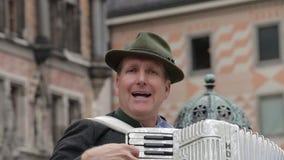 Un hombre del adulto juega un acordeón en un traje nacional metrajes