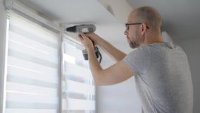 Un hombre del adulto sostiene un eléctrico perfora adentro sus manos y tornillos la ventana que lo protege contra luz almacen de metraje de vídeo