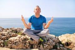 Un hombre del ajuste en la posición de Lotus respecto a una costa Hombre joven de la aptitud que hace yoga al aire libre Fotografía de archivo libre de regalías