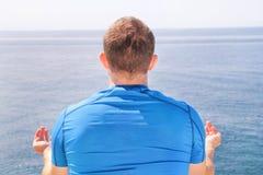 Un hombre del ajuste en la posición de Lotus respecto a una costa Hombre joven de la aptitud que hace yoga al aire libre Foto de archivo