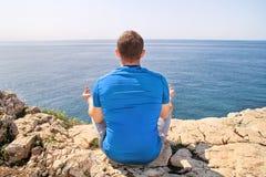 Un hombre del ajuste en la posición de Lotus respecto a una costa Hombre joven de la aptitud que hace yoga al aire libre Foto de archivo libre de regalías