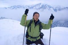 Un hombre del backpacker que entra en montañas del invierno Imagen de archivo libre de regalías
