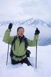 Un hombre del backpacker que entra en montañas del invierno Fotos de archivo