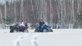 Un hombre del bosque A del invierno que tiene un problema con moto de nieve y la mujer que monta alrededor de él almacen de video