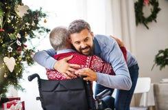Un hombre del inconformista que abraza a su padre mayor en silla de ruedas en el tiempo de la Navidad imagen de archivo