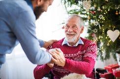 Un hombre del inconformista que da la bebida a su padre mayor en silla de ruedas en el tiempo de la Navidad fotos de archivo