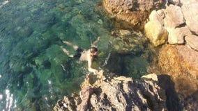 Un hombre del hombre joven que flota en la superficie del agua, de las estrellas de mar flotantes que flotan en una laguna exótic metrajes
