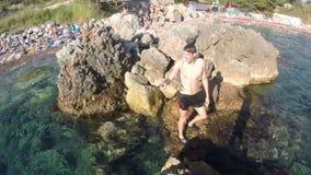 Un hombre del hombre joven que se coloca en tierra en rocas metrajes