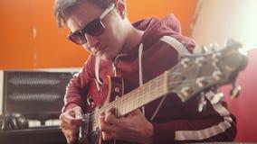 Un hombre del músico en los auriculares y los vidrios que tocan la guitarra y que registran la melodía en el estudio almacen de video