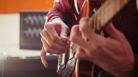 Un hombre del músico que toca la guitarra en el estudio y que registra el sonido