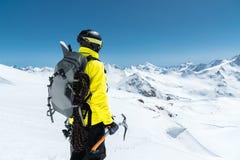 Un hombre del montañés sostiene un hacha de hielo alta en las montañas cubiertas con nieve Visión desde la parte posterior al air imagen de archivo libre de regalías
