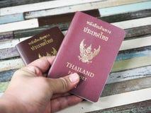 Un hombre del viaje que sostiene el pasaporte de Tailandia Foto de archivo libre de regalías