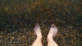 Un hombre descalzo se coloca en una costa pebbled en el agua, el agua lava los pies del hombre s, en primer almacen de video