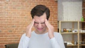 Un hombre desesperado joven que tiene dolor de cabeza, tensión del frustraion almacen de metraje de vídeo