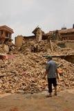Un hombre despeja a través de los escombros en Bhaktapur, Nepal Foto de archivo libre de regalías