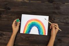 Un hombre dibuja un arco iris usando las pinturas y las brochas del aguazo fotos de archivo libres de regalías