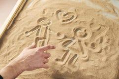 Un hombre dibuja por su finger en la arena Fotos de archivo libres de regalías