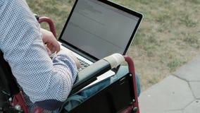 Un hombre discapacitado se está sentando en una silla de ruedas y está trabajando en un ordenador portátil en el parque metrajes