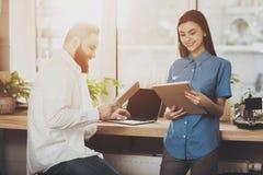 Un hombre discute asuntos del trabajo con una muchacha foto de archivo