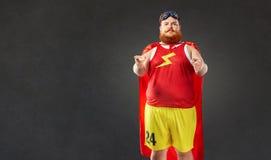 Un hombre divertido gordo en un traje del super héroe señala una mano en usted Fotos de archivo