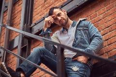 Un hombre elegante hermoso que lleva una chaqueta del dril de algodón que presenta en las escaleras afuera, mirando una cámara foto de archivo libre de regalías