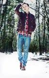 Un hombre elegante joven que camina a través de bosque nevoso Foto de archivo libre de regalías