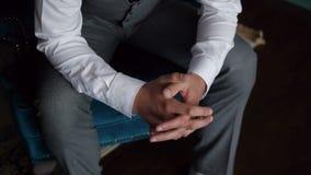 Un hombre elegante vestido que se sienta en una silla en un interior hermoso Primer de las manos dobladas en una cerradura