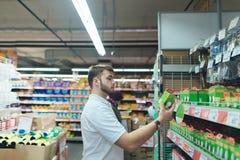 Un hombre elige las mercancías para una casa en un supermercado El hacer compras en la tienda imágenes de archivo libres de regalías
