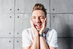 Un hombre emocional alegre divertido atractivo joven guiña en un s blanco fotos de archivo libres de regalías