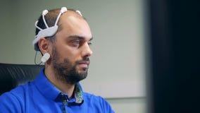 Un hombre en auriculares de la exploración de la onda cerebral está actuando un ordenador