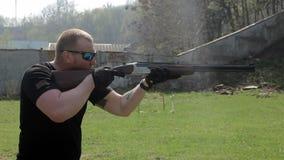 Un hombre en blancos y lanzamientos de los vidrios con un rifle de dos cañones A cámara lenta almacen de video