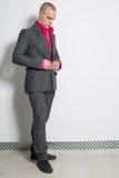 Un hombre en botones de una camisa del rojo forma el traje gris Imagenes de archivo