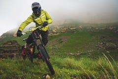 Un hombre en un casco de la montaña que monta una bici de montaña monta alrededor de la naturaleza hermosa en tiempo nublado down fotografía de archivo