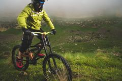 Un hombre en un casco de la montaña que monta una bici de montaña monta alrededor de la naturaleza hermosa en tiempo nublado down imagen de archivo libre de regalías