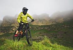 Un hombre en un casco de la montaña que monta una bici de montaña monta alrededor de la naturaleza hermosa en tiempo nublado down imagen de archivo