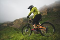 Un hombre en un casco de la montaña que monta una bici de montaña monta alrededor de la naturaleza hermosa en tiempo nublado down fotografía de archivo libre de regalías