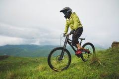 Un hombre en un casco de la montaña que monta una bici de montaña monta alrededor de la naturaleza hermosa en tiempo nublado down imagenes de archivo