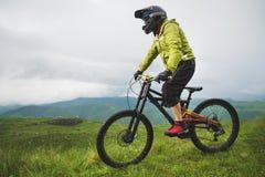 Un hombre en un casco de la montaña que monta una bici de montaña monta alrededor de la naturaleza hermosa en tiempo nublado down fotos de archivo