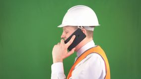 Un hombre en un chaleco protector blanco del casco y de la señal que habla en el teléfono en un emplazamiento de la obra, fondo v metrajes