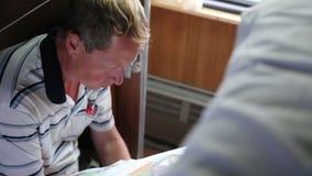 Un hombre en un coche de tren lee un periódico almacen de video